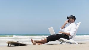Um homem com celular e computador trabalhando na praia