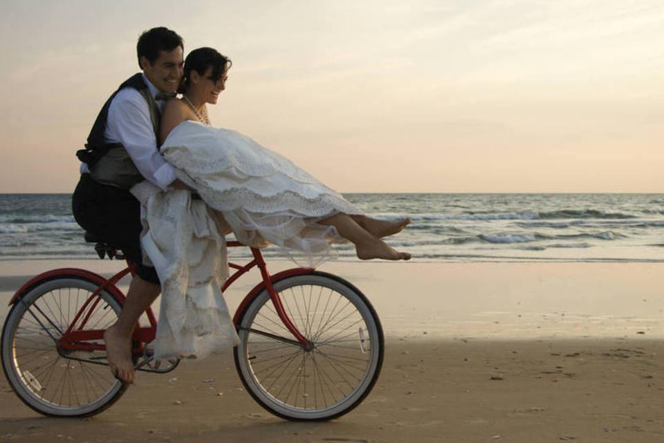 Noivos felizes em bicicleta na praia
